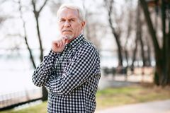 Musing senior man doubting. Where to go. Thoughtful senior man posing in park and touching face royalty free stock images