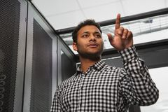 Musing IT technician tallying server closet. Serving facility. Low angle of meditative IT technician counting in server room and pointing with finger royalty free stock image