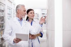 Musing two pharmacists collaborating. Meditative two pharmacists using tablet while working together stock photo