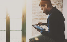 Musing young African American freelancer touching display of digital tablet while working in new project at home.Black. Businessman looking for information on stock images