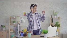 Musique énergique de écoute de jeune homme asiatique avec des écouteurs et la danse banque de vidéos