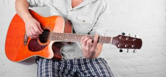 Musique - Br électrique orange de blanc de la corde D de joueur de guitare acoustique Photographie stock