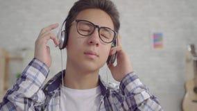 Musique calme de écoute de jeune homme asiatique de portrait avec des écouteurs clips vidéos