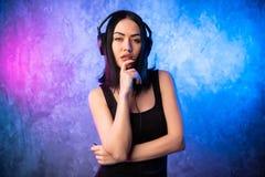 Musique de écoute de belle fille dans de grands écouteurs image libre de droits