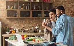 Musique de écoute de couples noirs affectueux pendant la cuisson du dîner dans la cuisine Photographie stock libre de droits