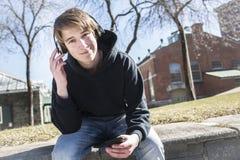 Musique de écoute d'ado et regarder le téléphone photo libre de droits
