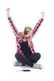 Musique de écoute d'adolescente heureuse dans des écouteurs d'isolement sur le petit morceau Photographie stock libre de droits