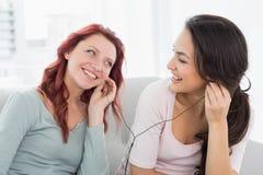Musique de écoute d'amis par des écouteurs ensemble à la maison Photographie stock libre de droits