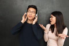 Musique de écoute d'homme asiatique insouciant par des écouteurs Photos libres de droits