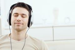 Musique de écoute d'homme avec des écouteurs Photos libres de droits