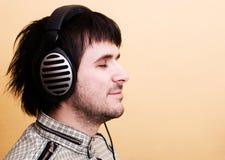 Musique de écoute d'homme dans des écouteurs photos stock