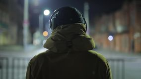 Musique de écoute d'homme méconnaissable dans des écouteurs à la ville de nuit clips vidéos