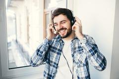 Musique de écoute d'homme occasionnel avec des écouteurs Images libres de droits