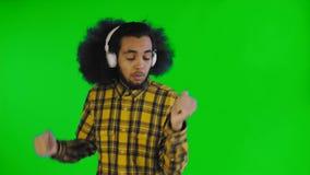 Musique de écoute d'homme positif d'Afro-américain dans des ses écouteurs sur l'écran vert ou le fond principal de chroma Concept clips vidéos