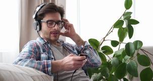 Musique de écoute d'homme sur l'appli et les écouteurs de téléphone portable banque de vidéos