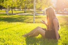 Musique de écoute de belle jeune femme en parc Photographie stock libre de droits