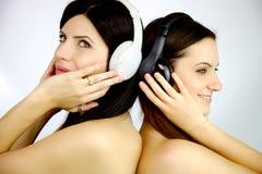 Musique de écoute de deux amies heureuses ensemble Photo stock