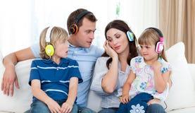 Musique de écoute de famille avec des écouteurs Photographie stock