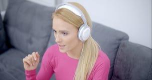 Musique de écoute de femme de téléphone utilisant le casque banque de vidéos
