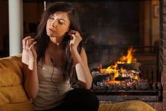 Musique de écoute de femme se reposant par la cheminée Photographie stock libre de droits