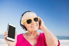 Musique de écoute de femme supérieure avec l'écouteur Photos stock