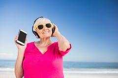 Musique de écoute de femme supérieure avec l'écouteur Photo libre de droits