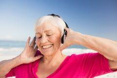 Musique de écoute de femme supérieure avec l'écouteur Photos libres de droits