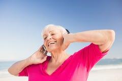 Musique de écoute de femme supérieure avec l'écouteur Photographie stock