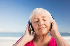 Musique de écoute de femme supérieure avec l'écouteur Image libre de droits