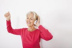 Musique de écoute de femme supérieure heureuse au-dessus du fond blanc Photos libres de droits