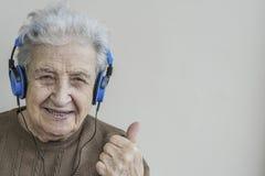 Musique de écoute de femme supérieure heureuse avec des écouteurs Images libres de droits