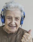 Musique de écoute de femme supérieure heureuse avec des écouteurs Photographie stock