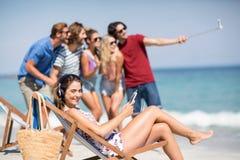 Musique de écoute de femme tandis qu'amis prenant le selfie à la plage Image libre de droits