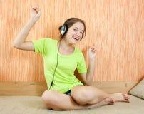 Musique de écoute de femmes heureux dans des écouteurs Photos libres de droits
