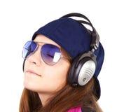 Musique de écoute de fille par des écouteurs au-dessus de blanc Image stock