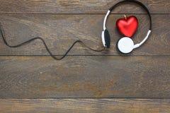 musique de écoute de forme rouge de coeur avec des écouteurs sur le bois Image libre de droits