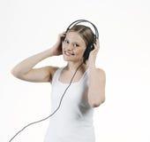 Musique de écoute de jeune femme avec des écouteurs Photo stock