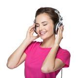 Musique de écoute de jeune femme gaie avec des écouteurs Photo libre de droits