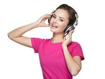 Musique de écoute de jeune femme gaie avec des écouteurs Photo stock