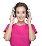 Musique de écoute de jeune femme gaie avec des écouteurs Photos stock