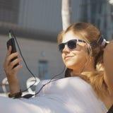 Musique de écoute de jeune fille attirante heureuse avec l'écouteur Images libres de droits