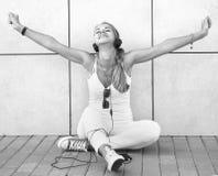 Musique de écoute de jeune fille attirante heureuse avec l'écouteur Photos stock