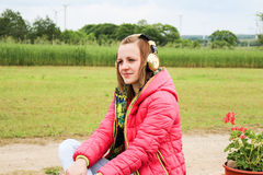 Musique de écoute de jeune fille dehors Photographie stock libre de droits