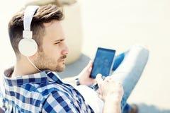 Musique de écoute de jeune homme à l'extérieur Photos libres de droits