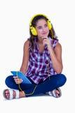 Musique de écoute de jolie brune réfléchie avec sa tablette image stock