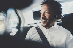 Musique de écoute de sourire belle d'homme africain sur le smartphone tout en se reposant sur la banquette arrière dans la voitur Photos stock