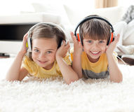 Musique de écoute de sourire d'enfants de mêmes parents avec des écouteurs Images stock