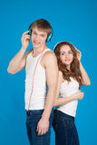 Musique de écoute de sourire heureuse de garçon et de fille dans des écouteurs dans Image stock