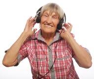 Musique de écoute drôle de vieille dame Photographie stock