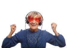 Musique de écoute drôle de vieille dame et de représentation pouces  Photos libres de droits